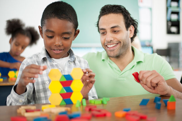 Male teacher helping young student to play with  blocks.