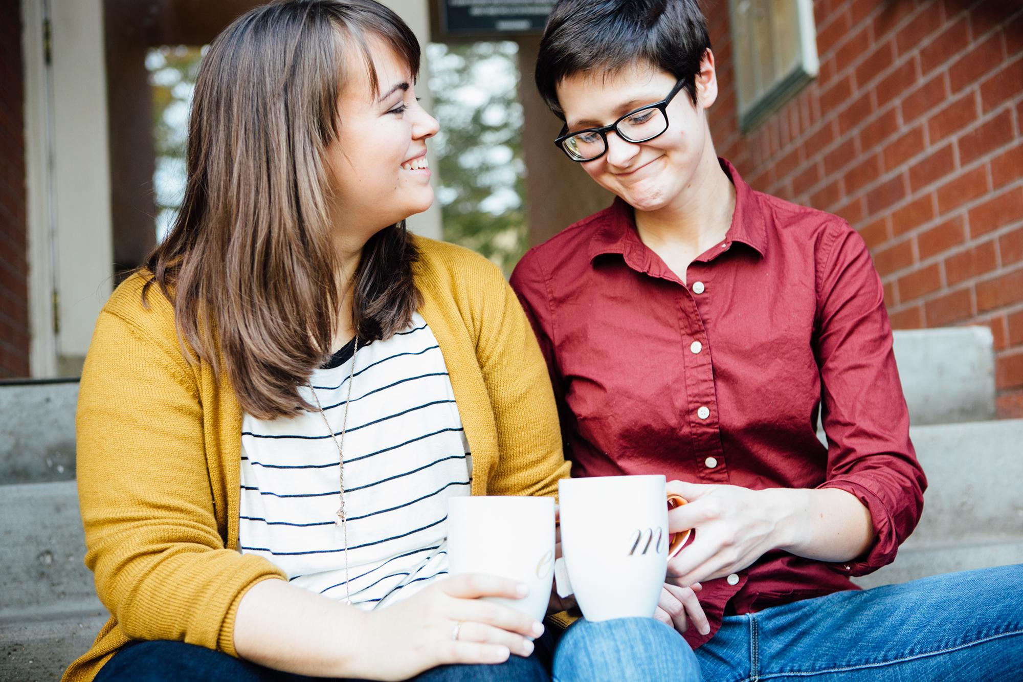 Two women clink mugs on steps outside building.