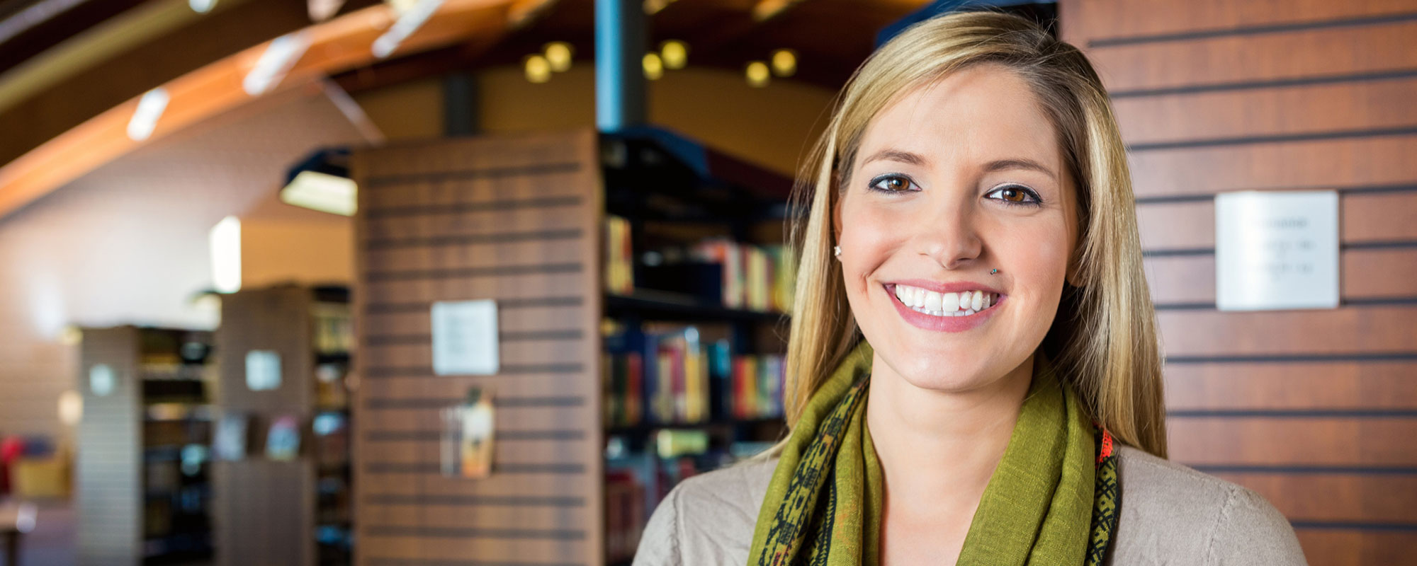 Woman standing in library smiling