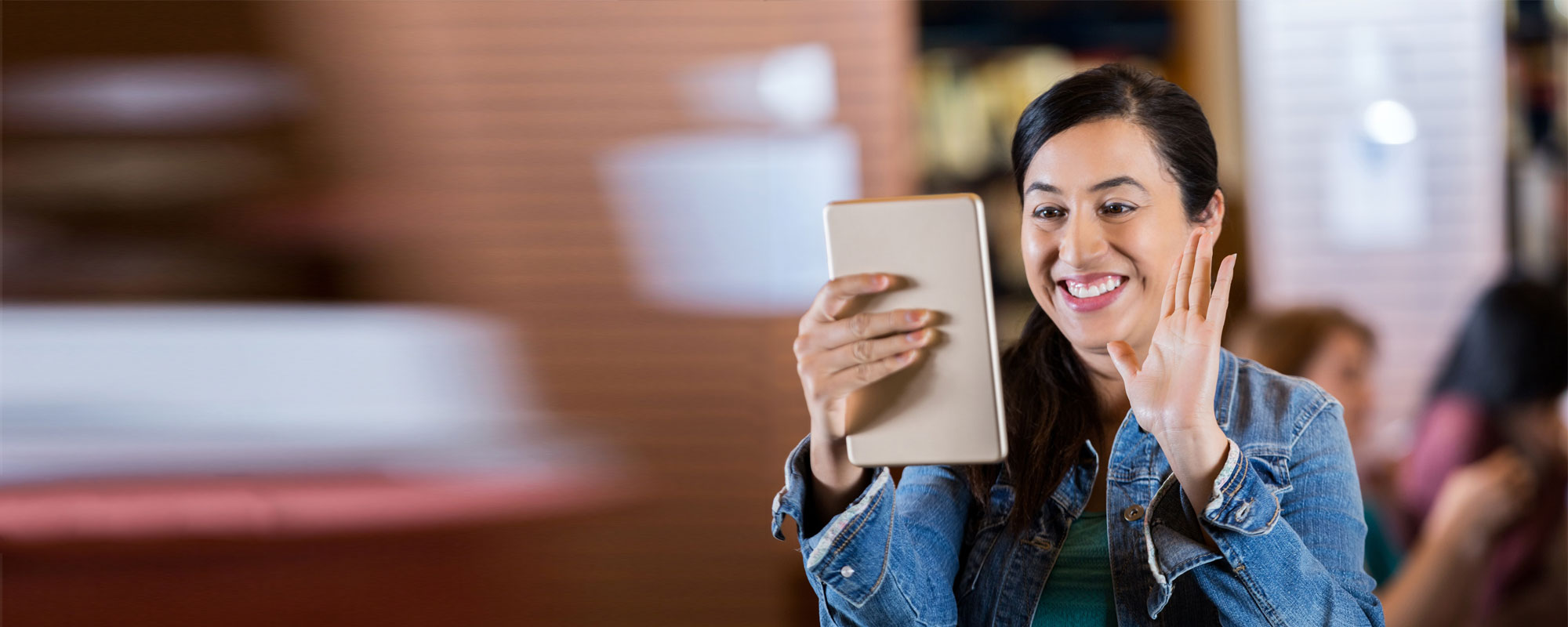 Young female in blue jean jacket holds up tablet and waves on video call.