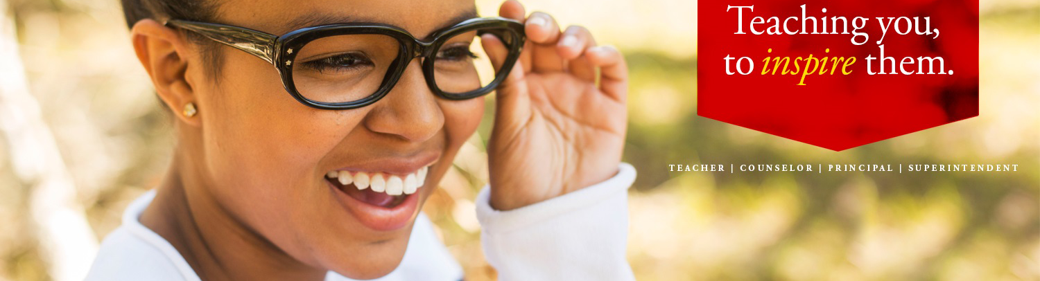 Woman of color laughing with glasses and red badge.