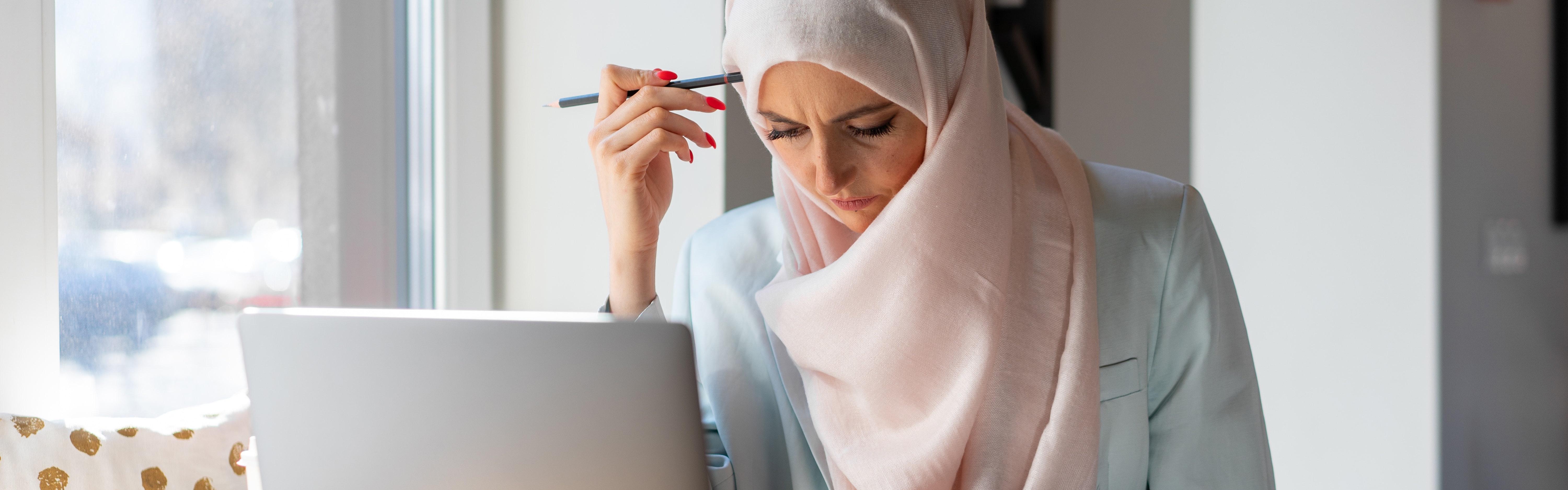 A Muslim woman sits at a laptop studying for her Colorado content area assessment.