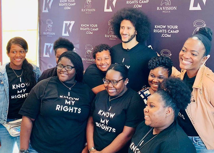 """A group of students with """"I know my rights"""" t-shirts, posing for a photo with football start Colin Kaepernick"""