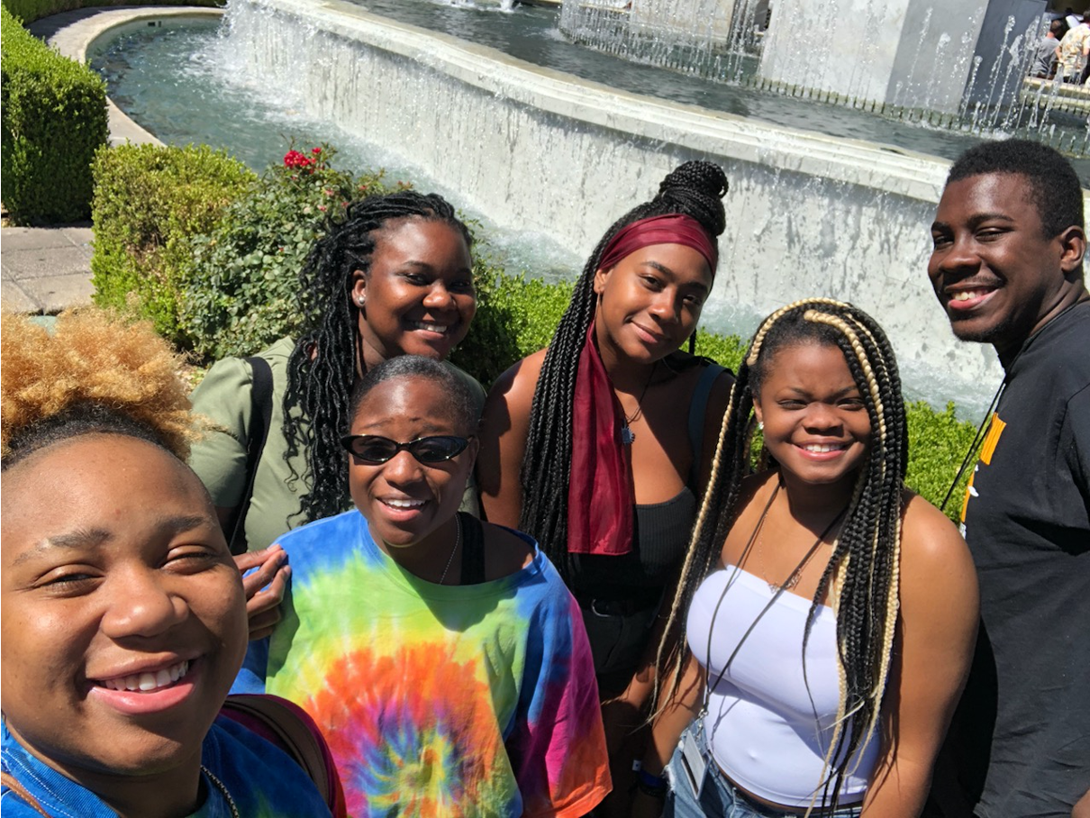 Several high school students taking a selfie near a water fountain; all smiling